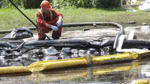 In this July 29, 2010, file photo, a worker watches water come out of a pipe in Talmadge Creek where booms have been set up to contain an oil spill in Marshall Township, Mich., near the Kalamazoo River.