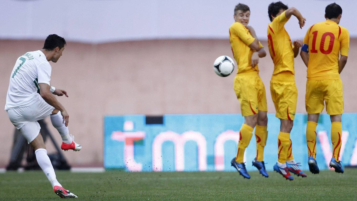 Portugal's Cristiano Ronaldo (L) takes a free kick in front of Macedonia's (from L) Stefan Ristovski, Stefan Spirovski and Goran Pandev during their international friendly soccer match at Magalhaes Pessoa stadium in Leiria May 26, 2012. The game ended in a 0-0 tie. REUTERS/Jose Manel Ribeiro