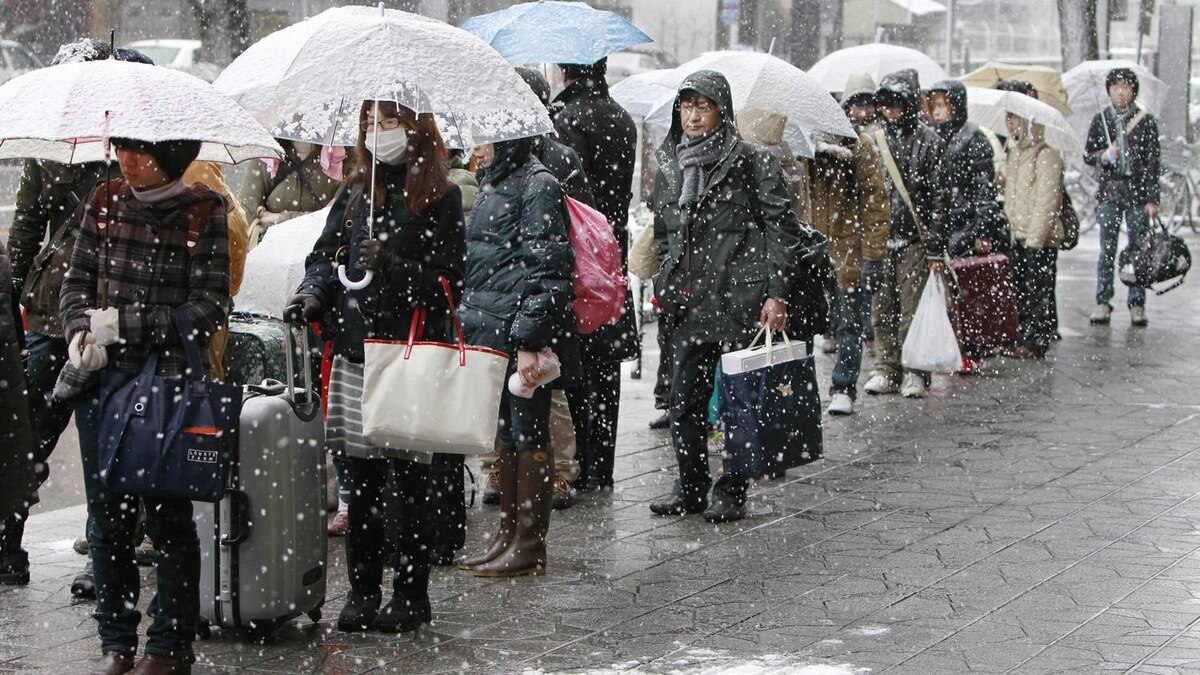 People stand in driving snow as they queue for a bus to leave town in Sendai, Japan, Thursday, March 17, 2011.