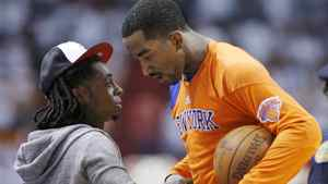 Rapper Lil Wayne (L) speaks with New York Knicks guard J.R. Smith during a break in play between the Knicks and the Miami Heat during Game 1 of their first round NBA Eastern Conference basketball playoff in Miami, Florida April 28, 2012. REUTERS/Andrew Innerarity