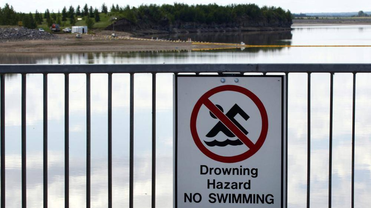 A no-swimming sign hangs on the banks of a lake near Innisfail, Alta., while a boom stretches out to contain a pipeline leak on June 12, 2012.