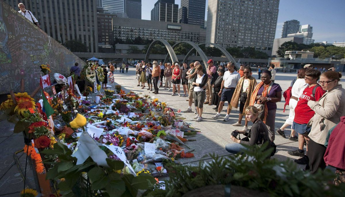 People pay their respects at a vigil for Jack Layton at Nathan Phillips Square prior to the funeral of the late NDP leader.