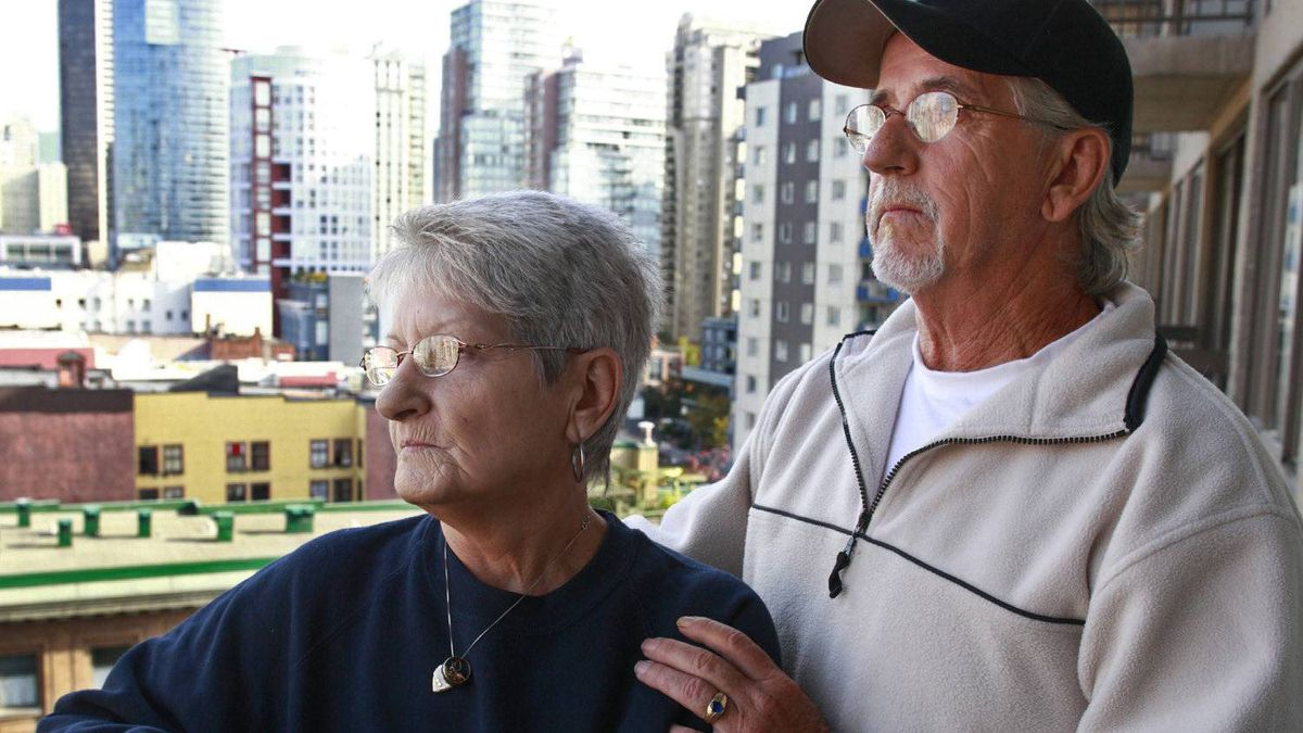 Rene Beaudoin (R) holds his wife Lilliane Beaudoin, as they look out over downtown Vancouver from their hotel October 14, 2011. Lilliane Beaudoin's adopted sister Dianne Rock is one of convicted serial murderer Robert Pickton's victims.
