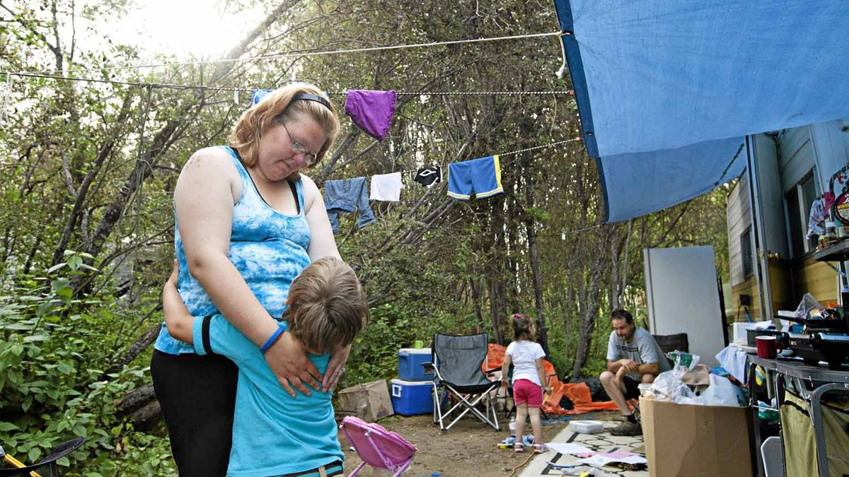 Lorraine Herd hugs her son Damon Parsons as daughter Mikayla Parsons and husband Kevin Parsons go about their daily routine at their Slave Lake, AB camp, August 21, 2011. The family of four is living at Big Fish Bay RV Park and was in a tent for 3 weeks until a nurse loaned them a camper trailer to stay in.