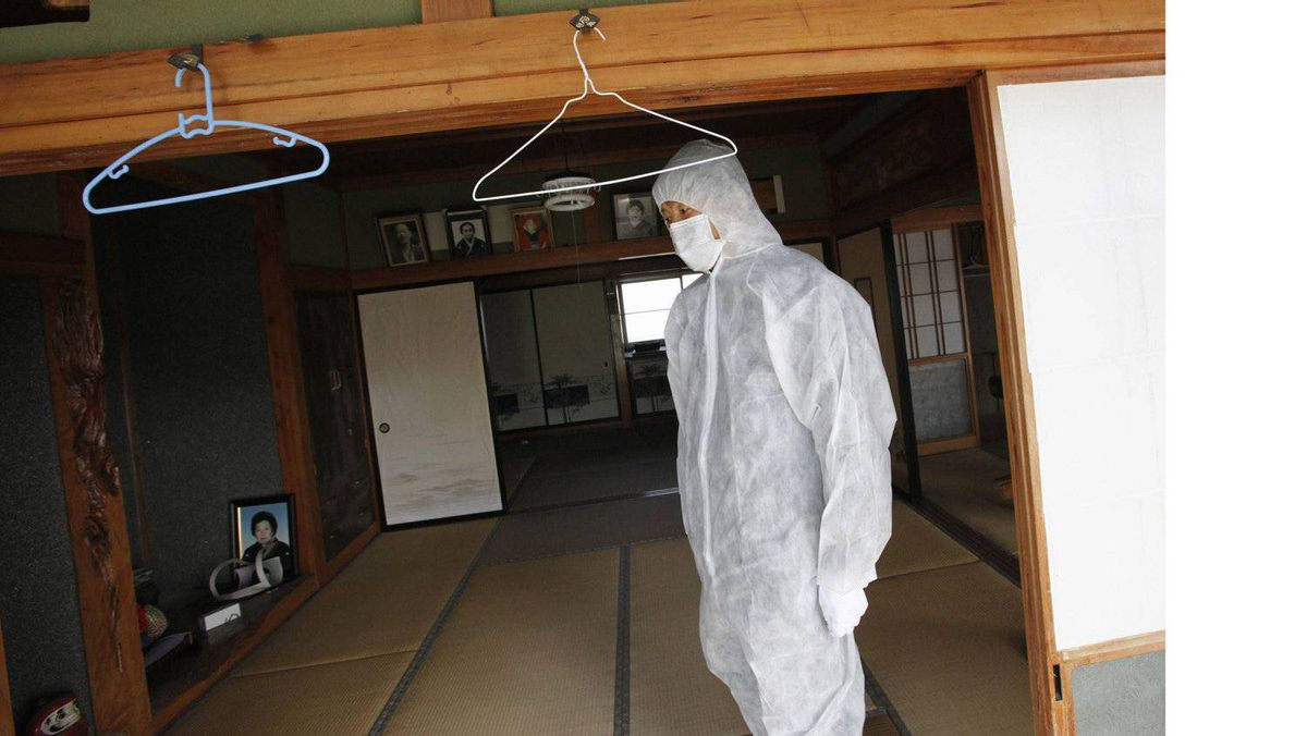 A resident, wearing a protective suit, makes a brief visit to the home in which he was evacuated from in Namie town.