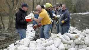 Volunteers sandbag a dike along the Assiniboine River in Brandon, Man., on April 9, 2011.