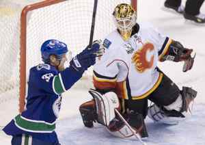 Vancouver Canucks Henrik Sedin, left, celebrates his brother Daniel Sedin's third period goal as Calgary Flames goaltender Curtis McElhinney looks on during NHL pre-season hockley action at GM Place in Vancouver, Monday, Sept. 21, 2009. The Canucks went on to win the game 5-4 in a shootout.