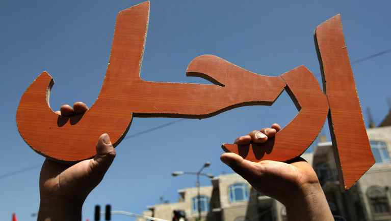 A Yemeni protester holds a wooden cutout that, in Arabic, reads in 'Leave.' It was hoisted during a massive anti-regime rally in the capital Sanaa on March 1, 2011.