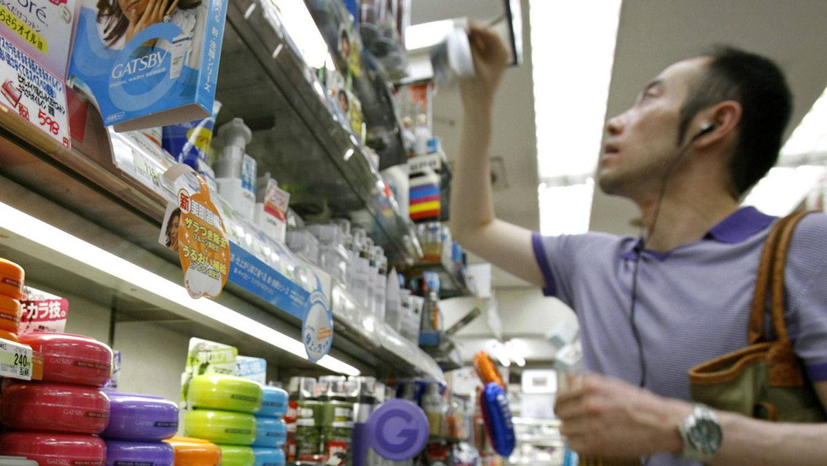 Cosmetics maker Mandom Corp.'s Gatsby Moving Rubber hair wax is seen on a shelf while a man picks up a cosmetic product for men at a drug store in Tokyo August 5, 2007.