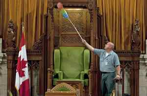 A worker dusts the Speaker's chair on Sept. 16, 2010, as the House of Commons chamber is prepared for the resumption of Parliament in Ottawa.