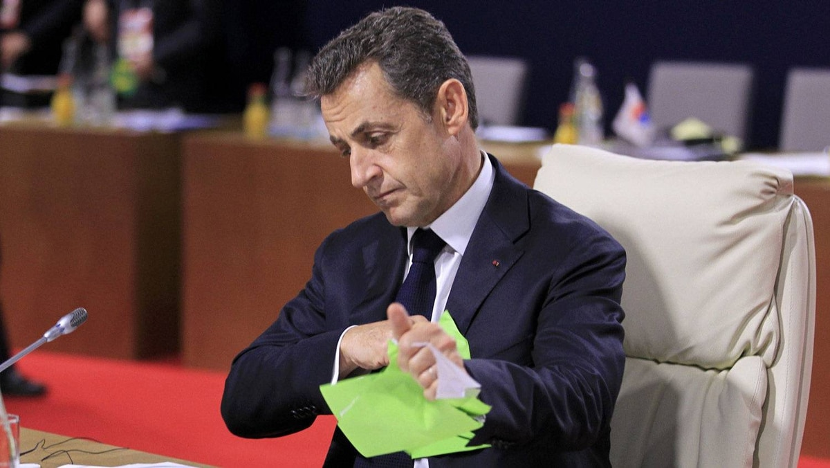 French President Nicolas Sarkozy tears up some papers as he waits talks to start.