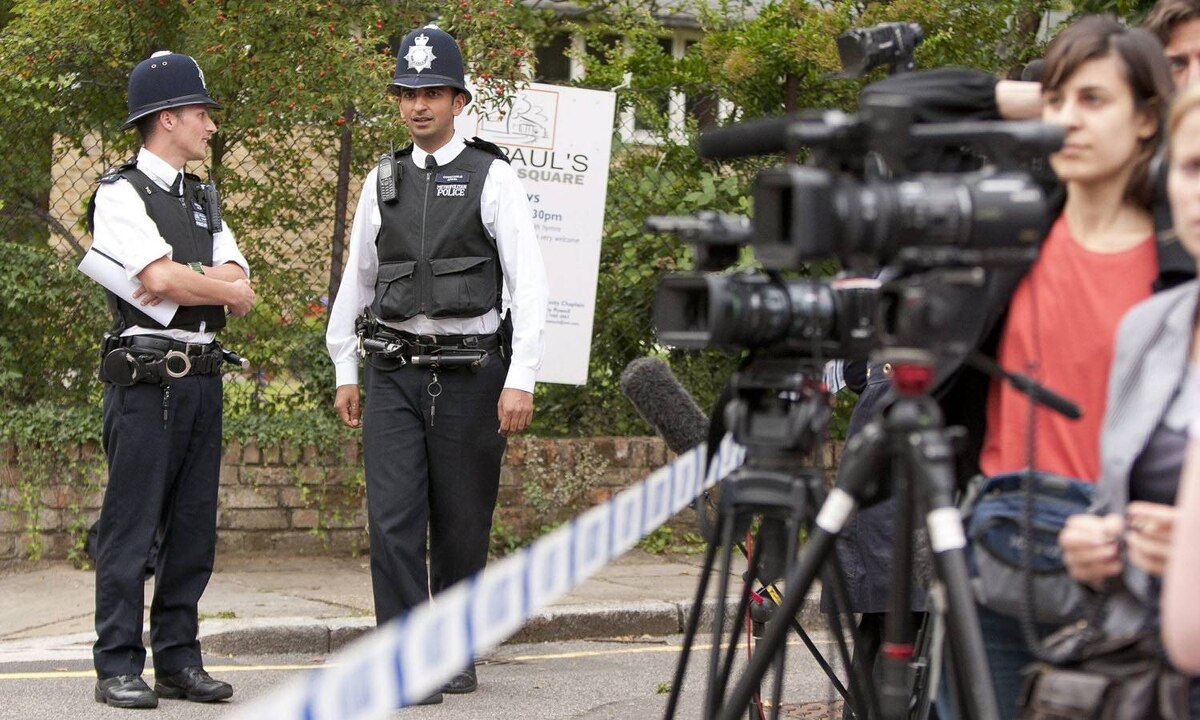 Police officers and media stand outside the home of Amy Winehouse in Camden Square on July 23, 2011. Her body was found earlier that day.