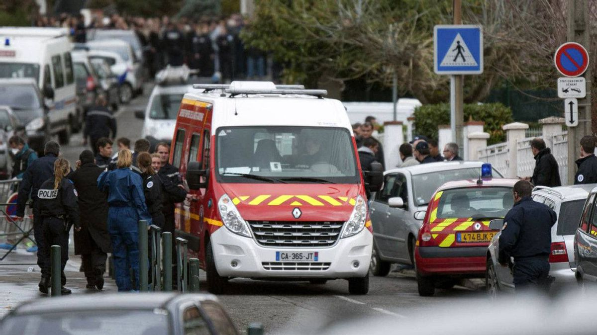 Police officers and firefighters gather at the site of a shooting near a Jewish school in Toulouse, southwestern France, on March 19, 2012.