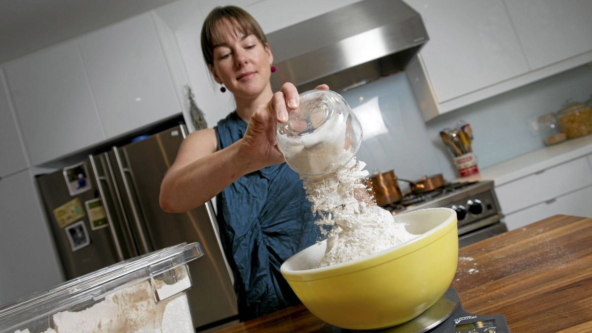 Chef Laura Calder pours flour into a mixing bowl on a kitchen scale.