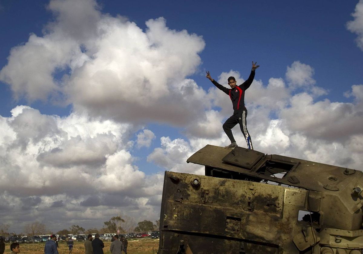 A Libyan boy reacts while standing on top of a destroyed military vehicle belonging to the forces of Moammar Gadhafi in the outskirts of Benghazi, eastern Libya, Sunday, March 20, 2011. (AP Photo/Anja Niedringhaus)