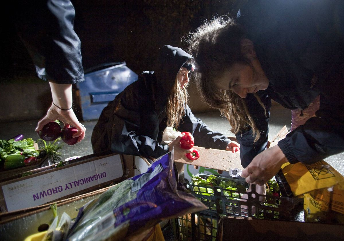 May Wollf (C) and Robin Pickell (R), practising 'freegans', sort through food they plucked out of a dumpster behind an organic grocery store in Coquitlam, British Columbia.