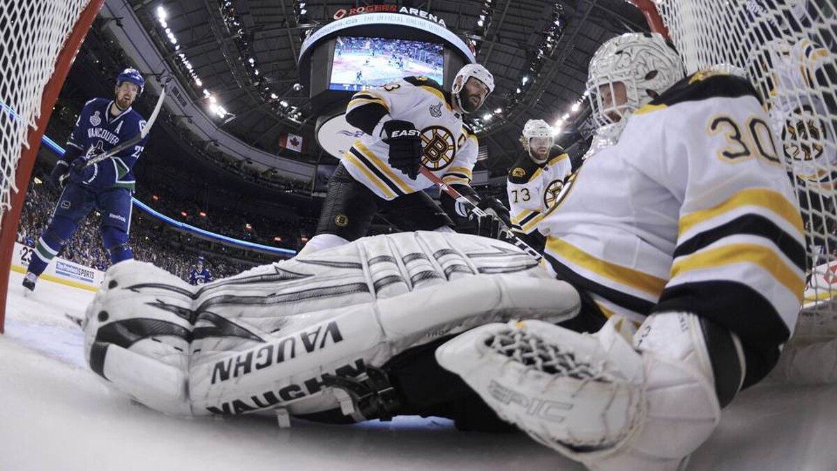 Boston Bruins goalie Tim Thomas falls into the net as he makes a save on Vancouver Canucks' Daniel Sedin.