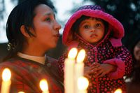A mother helps her child pray after placing candles at a cathedral in India.