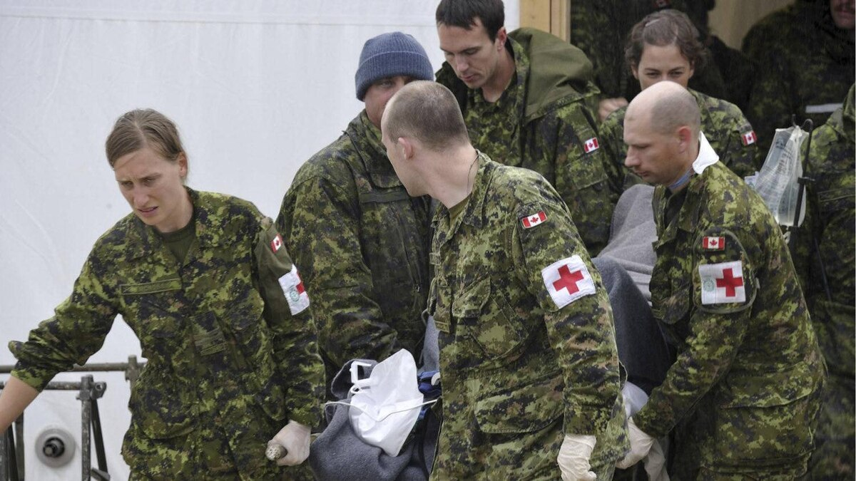 Members of the Canadian Armed Forces carry a victim of a plane crash in Resolute Bay, Nunavut, Saturday, Aug.20, 2011.