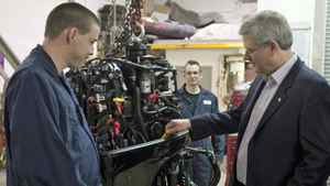 Conservative Leader Stephen Harper checks the oil on a marine engine as a mechanic looks on during a campaign stop in Regina on March 29, 2011.