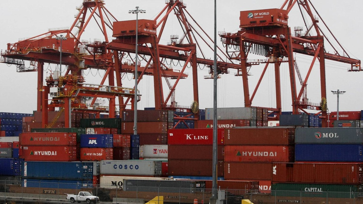 Cargo containers are stacked up as three cranes used to load and unload them from cargo ships tower above at the Port of Vancouver in Vancouver, B.C., in this file photo.