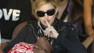 Madonna quietens adopted Malawian child Mercy James during a visit to Gumulira village, about 80 km from the Malawian capital of Lilongwe, during an April 2010 visit to the country.
