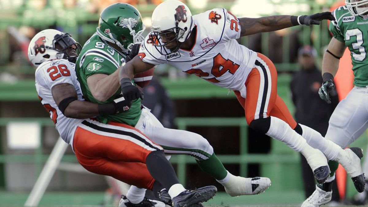 Saskatchewan Roughriders slotback Andy Fantuz, centre, gets taken down by BC Lions defensive back J.R. Ruffin and defensive back Korey Banks.
