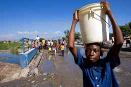 A boy carries a hard won bucket of water away from a broken water pipe in the commune of Cite Soleil in Port-au-Prince, Haiti.