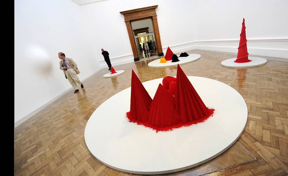 """Art enthusiasts admire an artwork entitled """"As If to Celebrate I Discovered a Mountain Blooming with Red Flowers 1981"""" a wood, cement, polystyrene and pigment sculpture."""