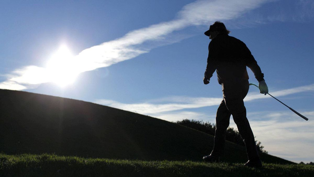 U.S. golfer Phil Mickelson walks into the sun rise over the 6th tee on Torrey Pines south course during play in the Pro-Am at the Farmers Invitational PGA golf tournament in San Diego January 25, 2012.