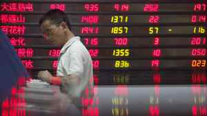 An investor checks stock information in front of an electronic board as his figure is reflected in a marble counter at a brokerage house in Wuhan, Hubei province, August 23, 2011.