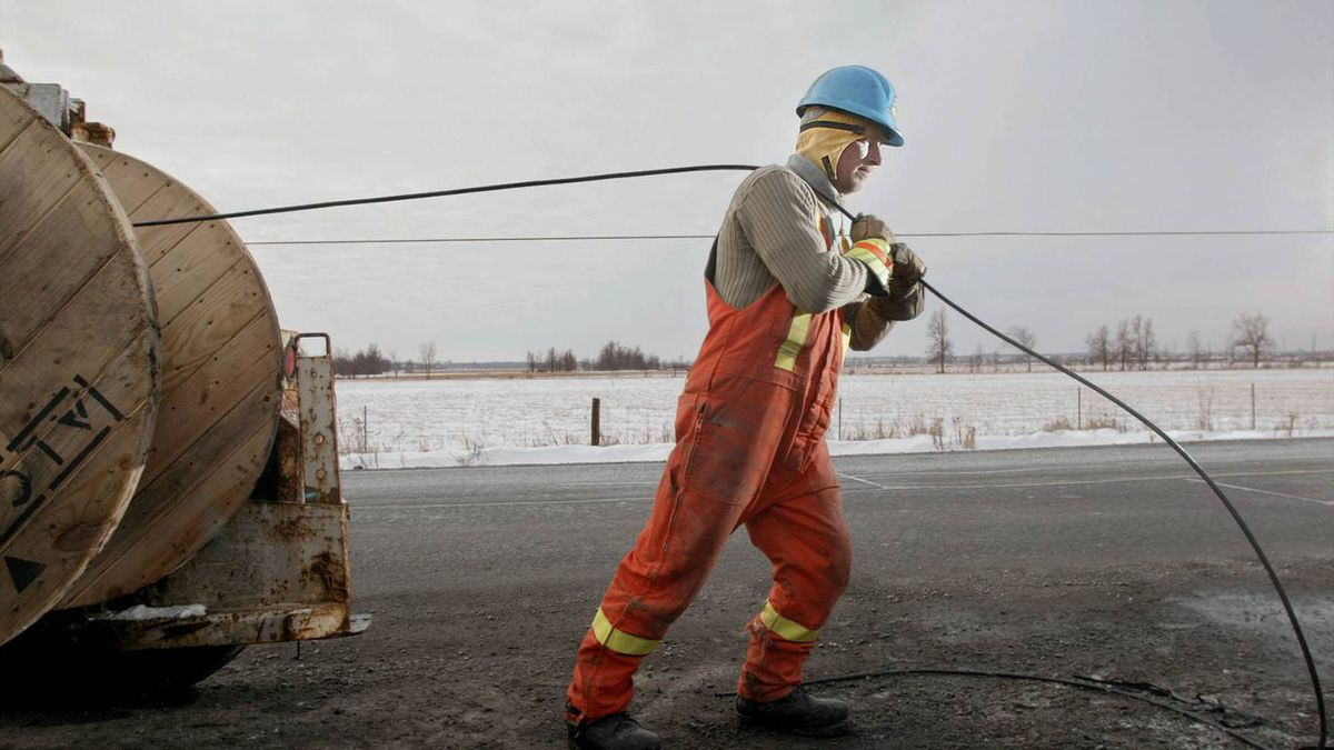 A telecom worker lays fibre-optic cable