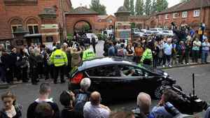 Media and members of the public gather outside the gates as family and friends arrive for the cremation of Amy Winehouse at Golders Green Crematorium on July 26, 2011 in London, England.