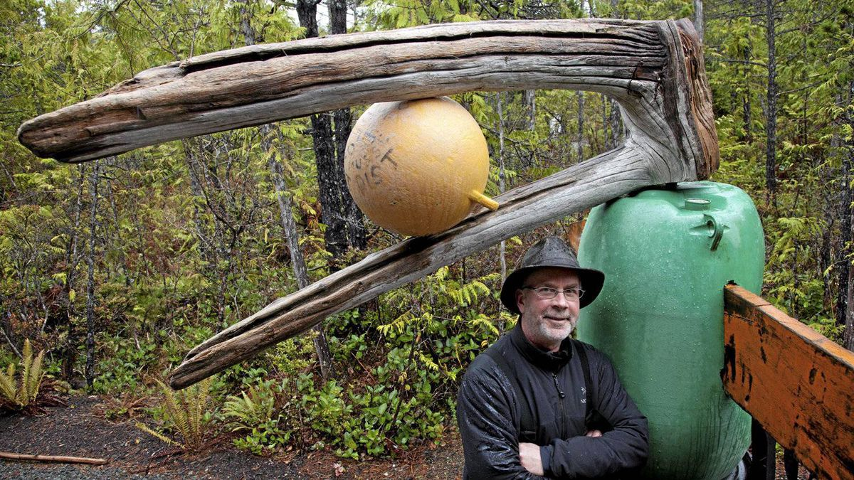 Artist Peter Clarkson poses with a portion of a totem pole that he has been building in Tofino, B.C. Tuesday, April, 17, 2012. The totem is being built out of debris that he finds along the beaches in the area with some items possibly being from the Japanese Tsunami.