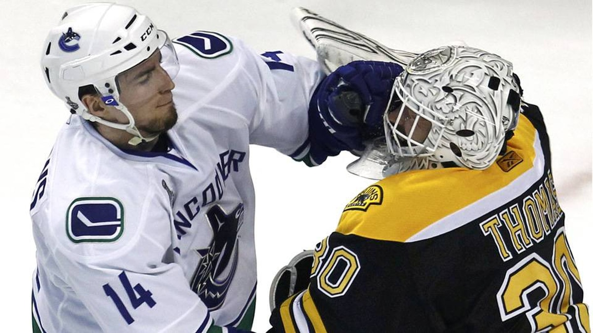 Vancouver Canucks left wing Alex Burrows and Boston Bruins goalie Tim Thomas fight in Game 4.