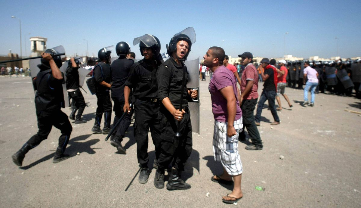 An Egyptian protestor argues with riot police outside the court set up in the Cairo Police Academy on the first day of the trial of Egypt's ousted president Hosni Mubarak and his two sons.