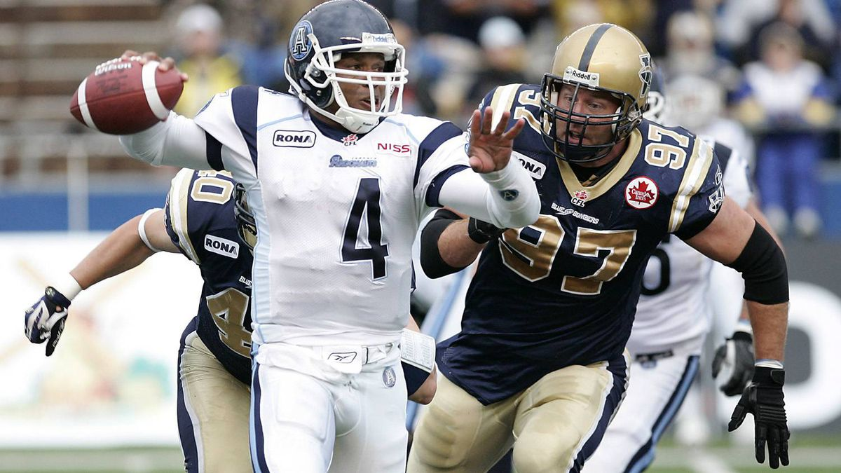 Toronto Argonauts QB Kerry Joseph (4) throws under pressure from Winnipeg Blue Bomber Doug Brown (97) and Cam Hall (40) during first half CFL action in Winnipeg Friday, June 27, 2008.