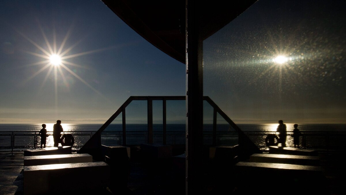 Passengers are reflected in a window shortly after sunrise aboard a B.C. Ferries vessel traveling from Tsawwassen to Swartz Bay on Friday August 26, 2011.