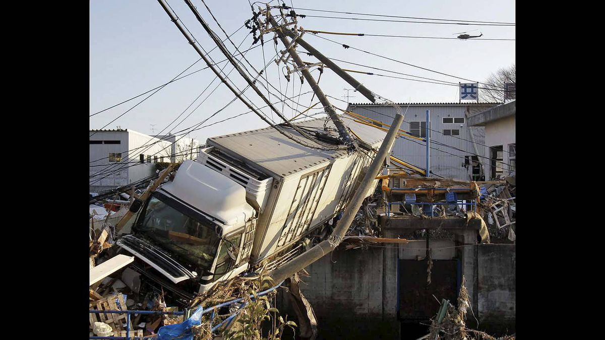 A huge trailer stuck in an narrow canal leans over debris at a port in Sendai, northern Japan, one day after a massive Tsunami triggered by a huge earthquake hit northern Japan Saturday, March 12, 2011.