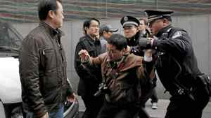 """A man (2nd R) is arrested by police after calls for a """"Jasmine Revolution"""" protest, organised through the internet, in front of the Peace Cinema in downtown Shanghai February 27, 2011."""