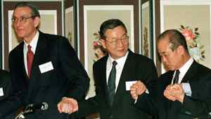 William (Bill) Rhodes, left, clasps hands with South Korean finance minister Lee Kyu-sung, centre, and chairman of the Korea Exchange Bank Hong Se-pyo in a show of unity after a signing ceremony for debt extension in Seoul, March 31, 1998.
