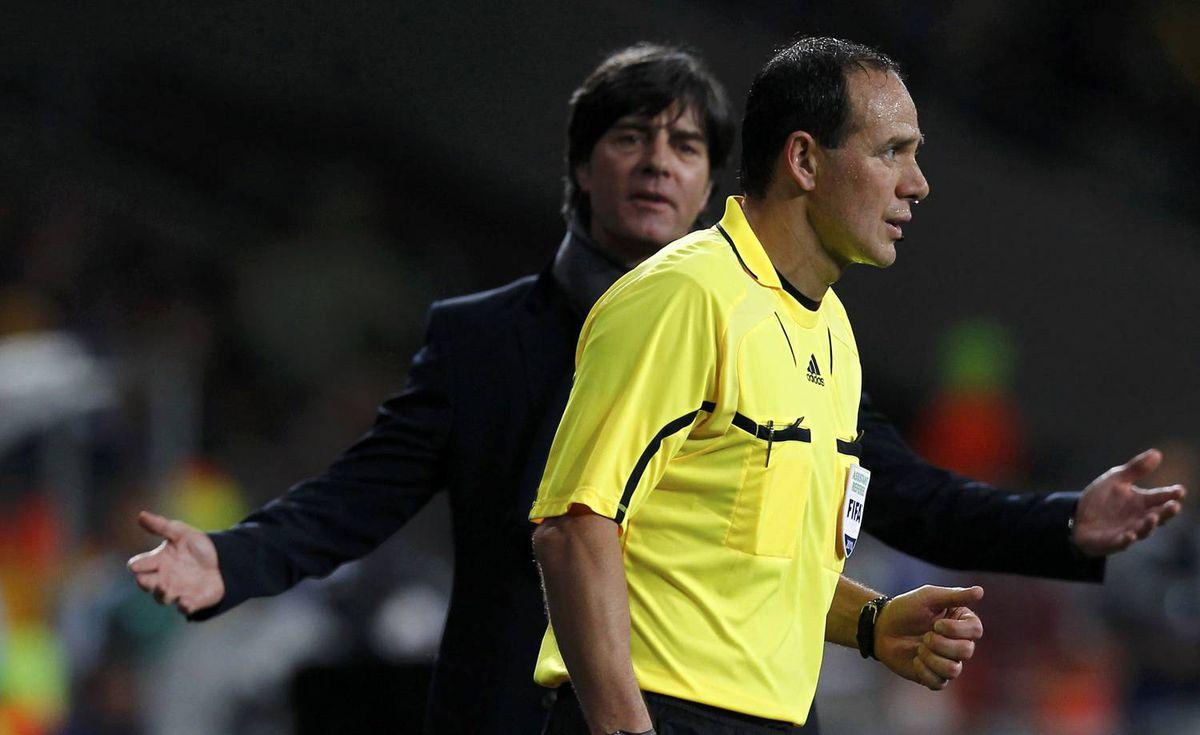 Germany's coach Joachim Loew (L) reacts next to assistant referee Hector Vergara of Canada during the 2010 World Cup third place playoff soccer match against Uruguay in Port Elizabeth July 10, 2010. REUTERS/Marcos Brindicci