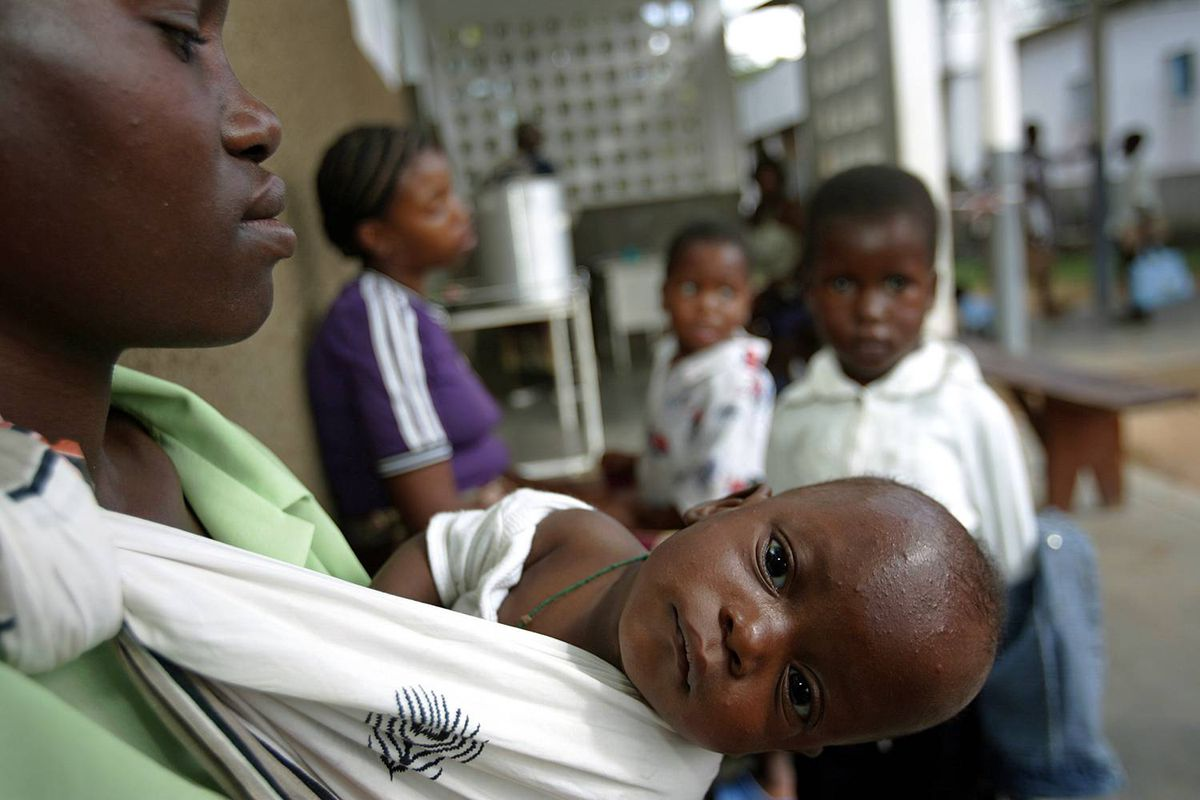 A mother waits with her child to be tested for malaria in Xai Xai, north of Maputo, in Mozambique on June 22, 2005.