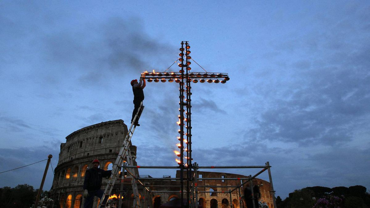 A worker lights a cross before Pope Benedict XVI leads a Via Crucis (Way of the Cross) procession during Good Friday celebrations in front of Colosseum in Rome April 6, 2012.