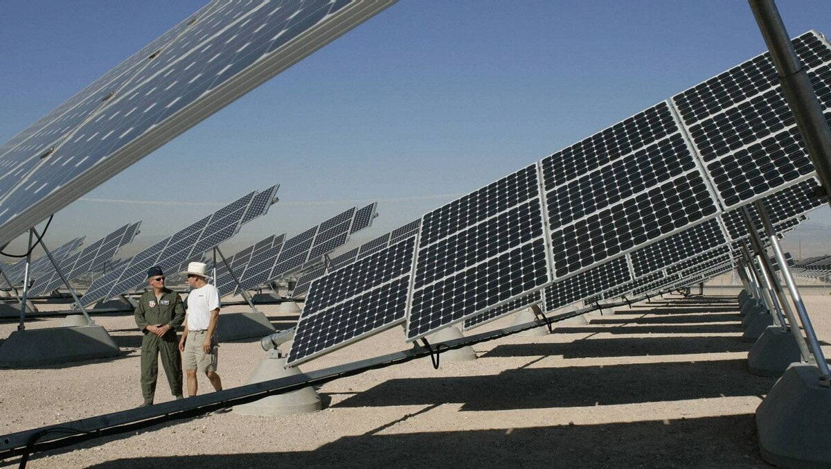 In this 2008 file photo, Col. Dave Belote (L), commander of Nellis Air Force Base, and Eric Vander Leest, a photovoltaic system technician for SunPower Corp., walk through an array of solar photovoltaic panels at the base in Las Vegas, Nevada.