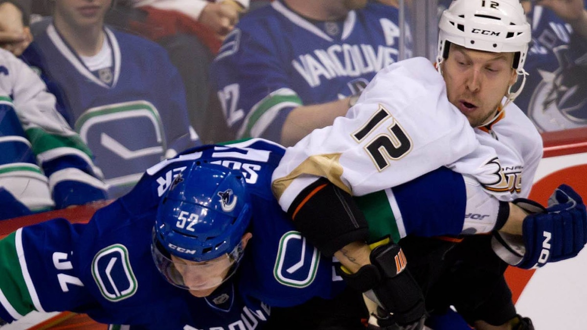 Anaheim Ducks' Niklas Hagman, right, of Finland, ties up Vancouver Canucks' Alexander Sulzer, of Germany, during the second period of an NHL hockey game in Vancouver, B.C., on Sunday January 15, 2012. THE CANADIAN PRESS/Darryl Dyck