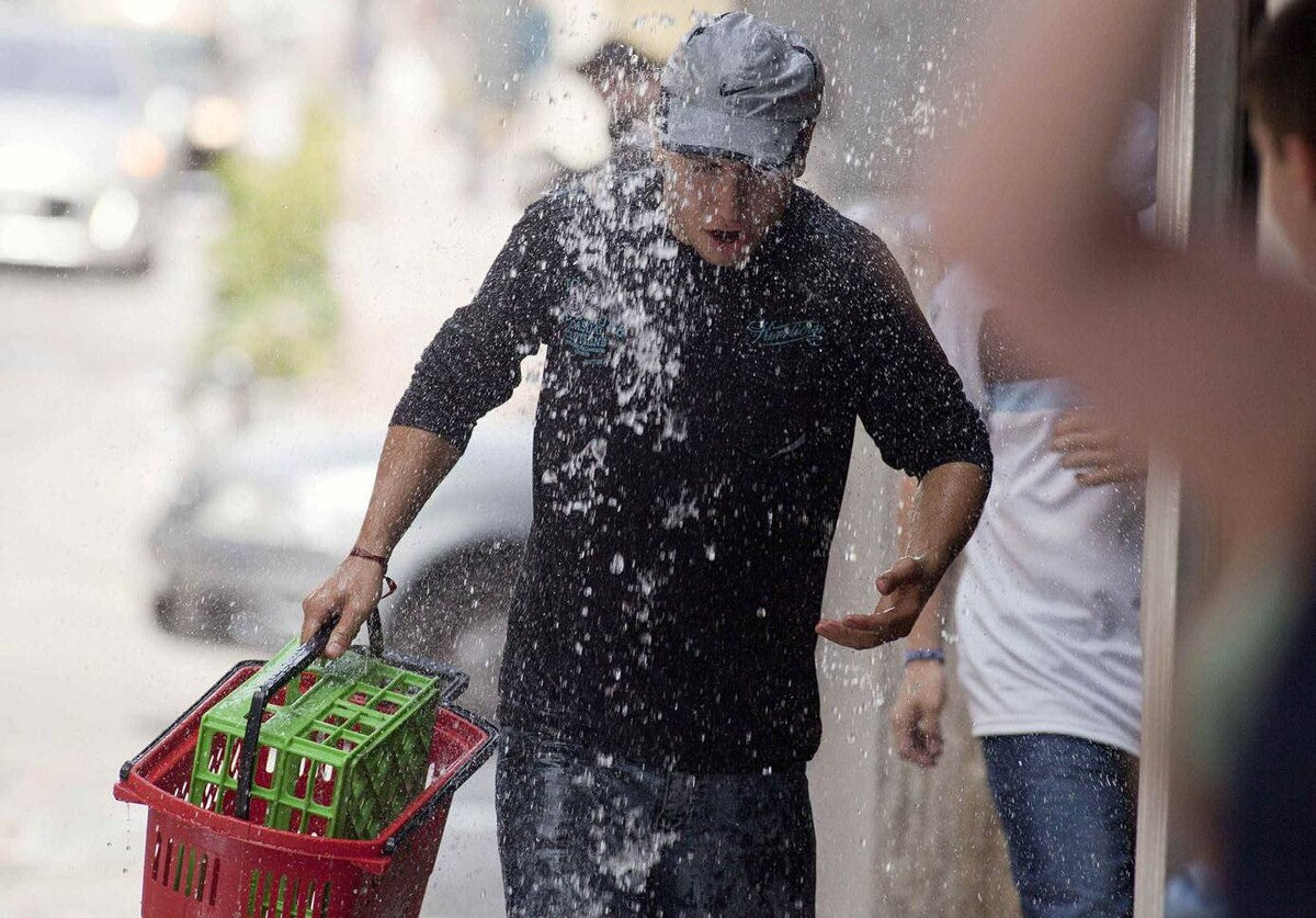 A pedestrian is soaked while walking through the financial district of Montevideo where workers throw water at each other to celebrate the end of the year.
