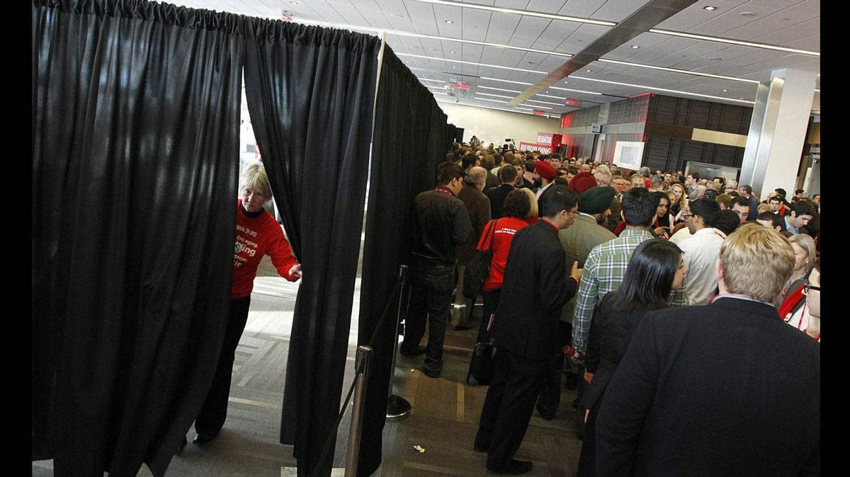 A volunteer peeks out from the area curtained- off for voting. The voting for Liberal party executive positions finally began about 30 minutes later than scheduled. Outside delegates wait in line for the voting to begin on day two of the Liberal Convention in Ottawa.
