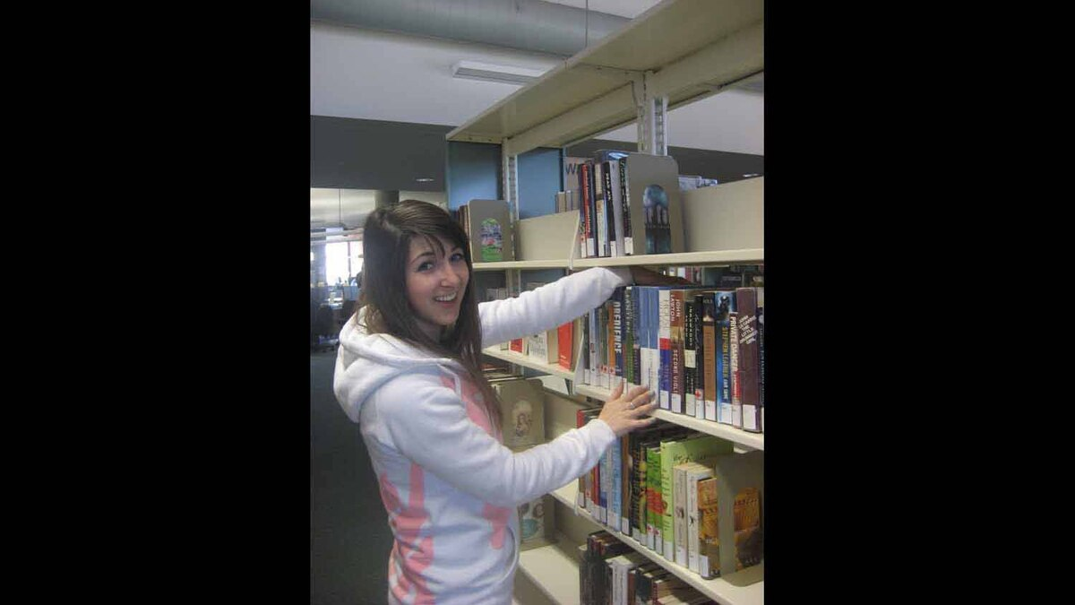 This future librarian spends some of her work day shelving books. Photo taken April 27, 2012
