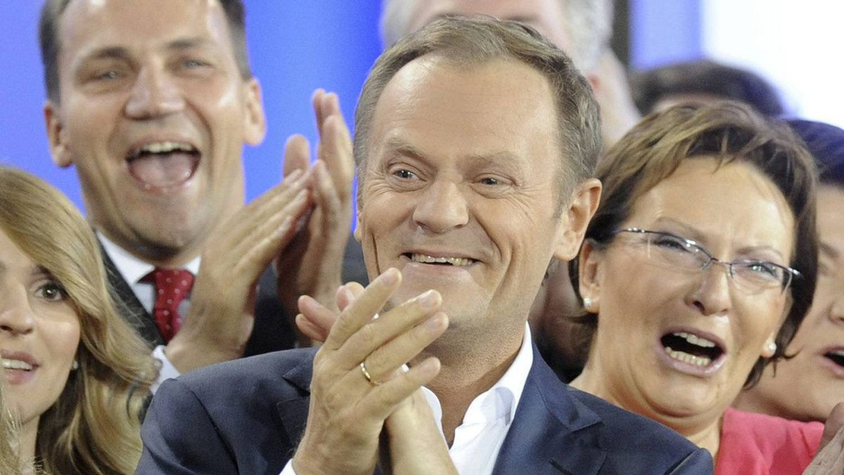 Prime Minister Donald Tusk, center, celebrates with Health Minister Ewa Kopacz, right, and Foreign Minister Radek Sikorski, background left, as the first exit poll is published during the election party of Tusk's Civic Platform, a centrist and pro-EU party, in Warsaw Sundey, Oct. 9, 2011.